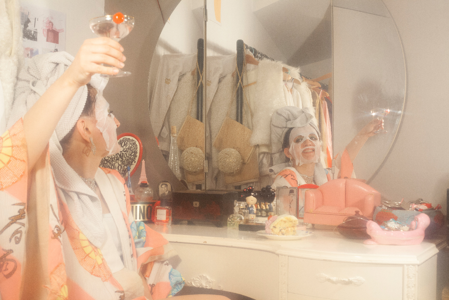 Woman wearing towel and face mask in front of mirror raising a cocktail glass