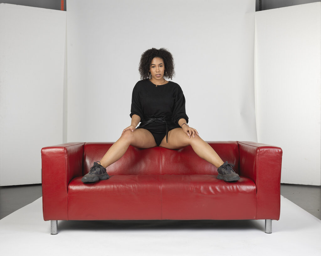 Woman manspreading on sofa