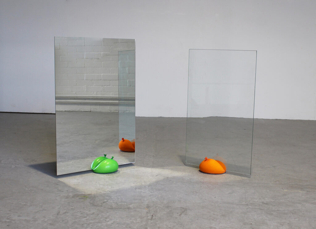 Two colourful ballon individually holding up one large mirror and one large pane of glass