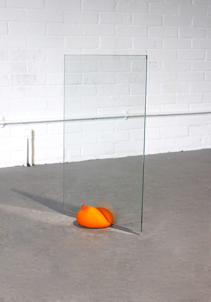 Large solid balloon holding up a large pane of glass in the middle of an empty room