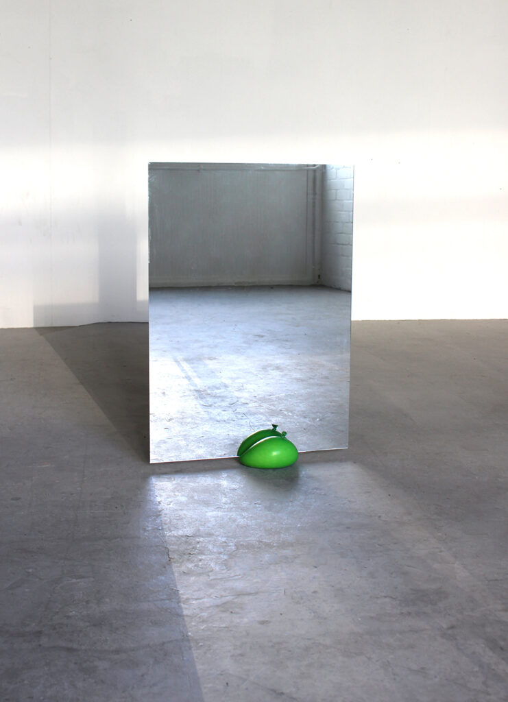 A single green balloon on the floor with a large mirror set in to it. The balloon is holding the mirror upright and a large empty room.