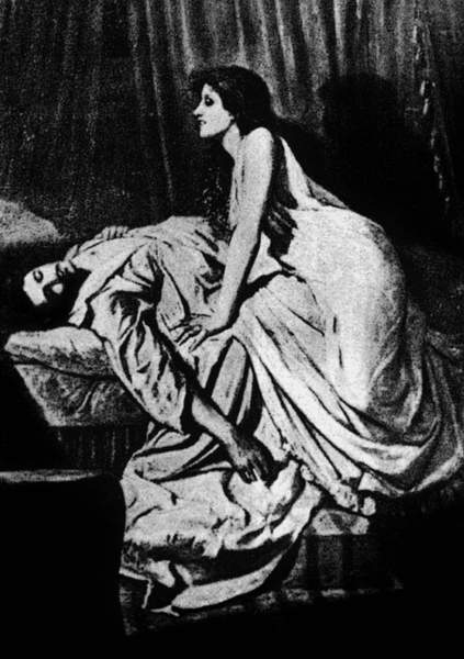 Man lying limp whilst vampire woman leans over him