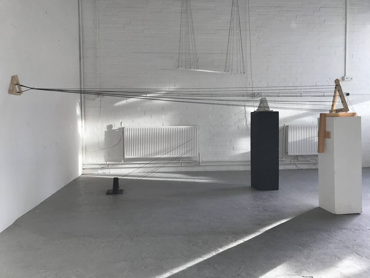 Photograph of a test of a sculpture. Triangles on a plinth connected to a wall with lines of wire.
