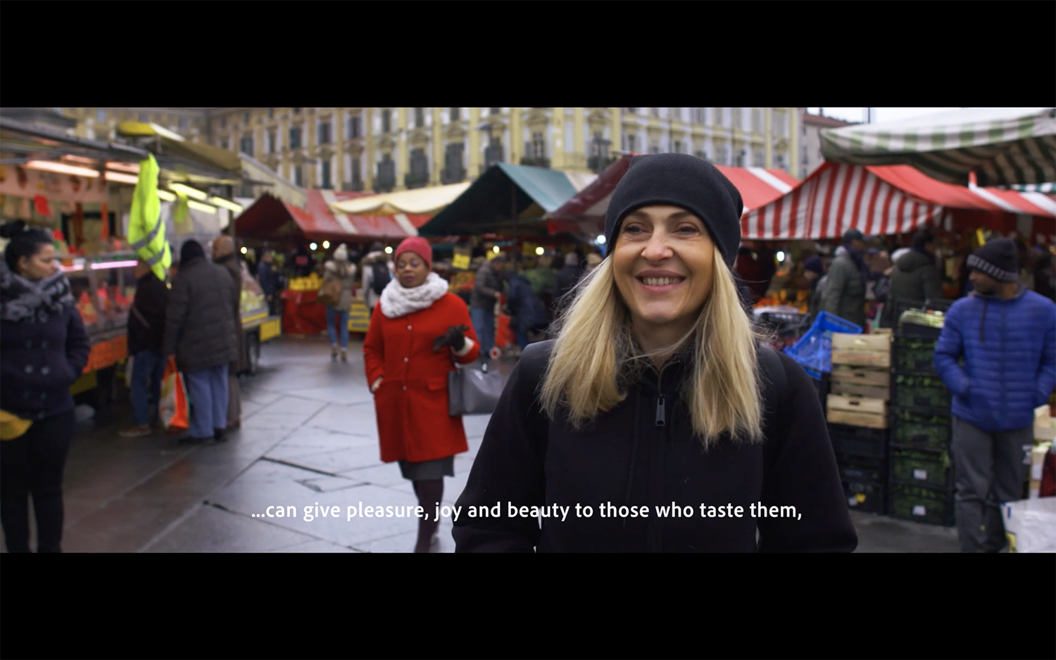 Lady in black hat being interviewed at market