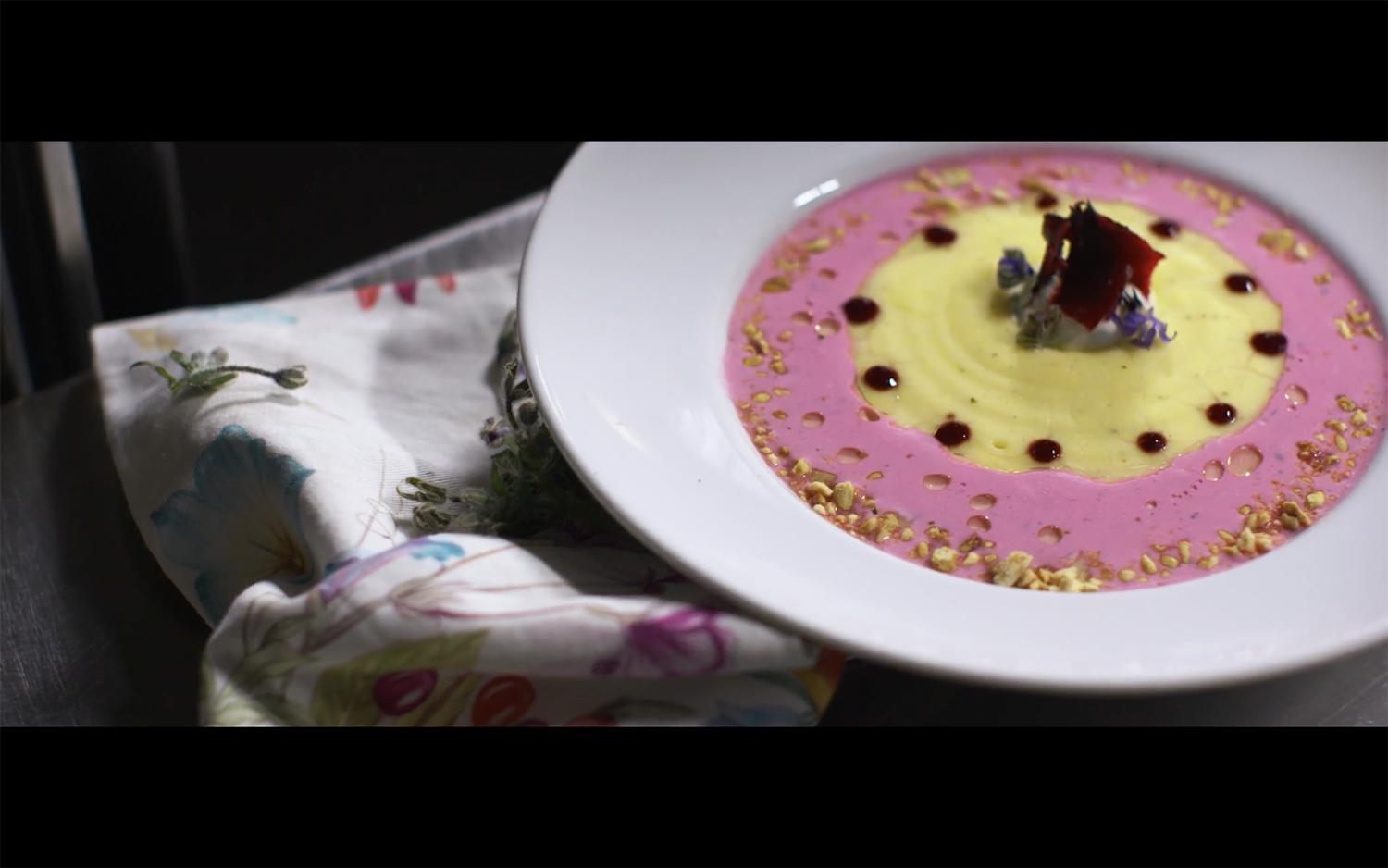 Dish of pink and yellow food on floral fabric