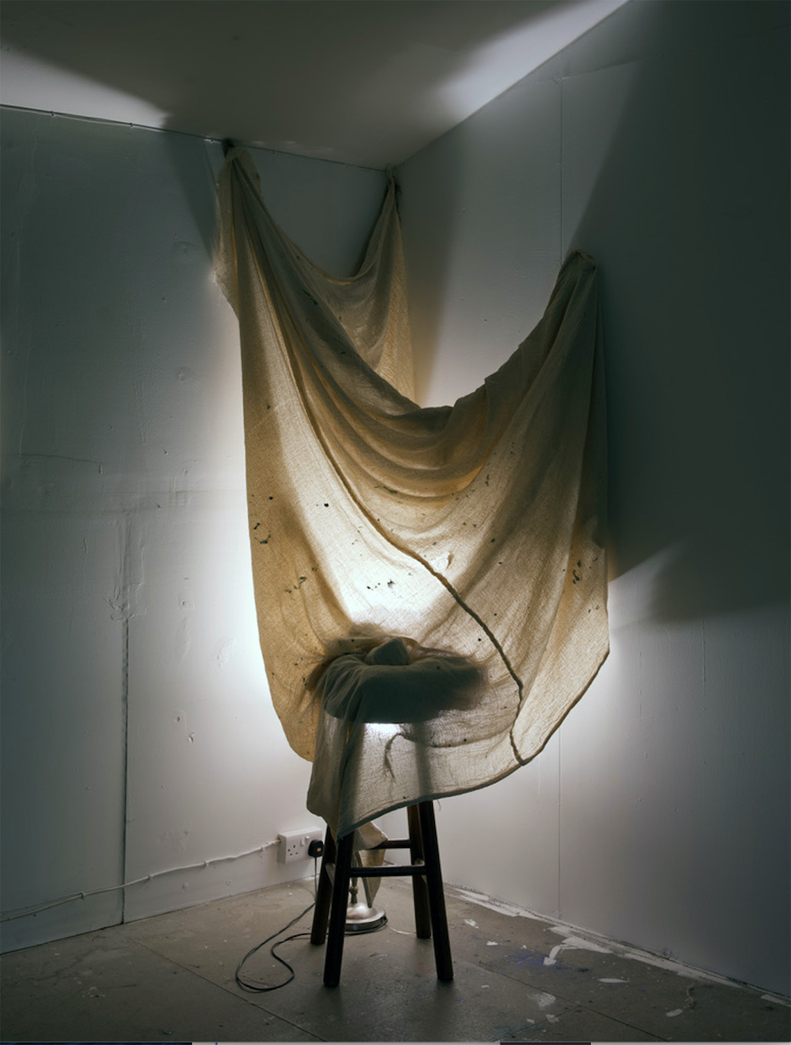 seat draped with cloth and light behind it